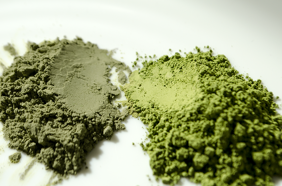 Two piles of matcha, on the right hand side is a vibrant glossy emerald green matcha and on the left hand side is a dull grey looking matcha.